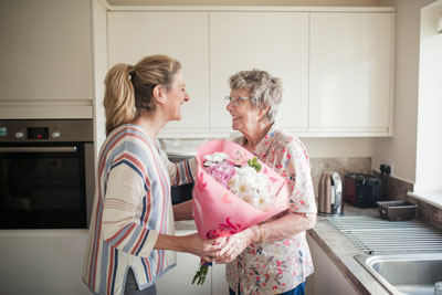 Caregiver handing flowers to woman