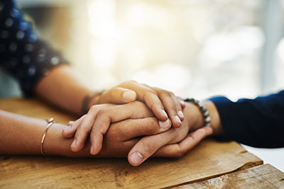 close-up of a caregiver clasping a senior woman's hands