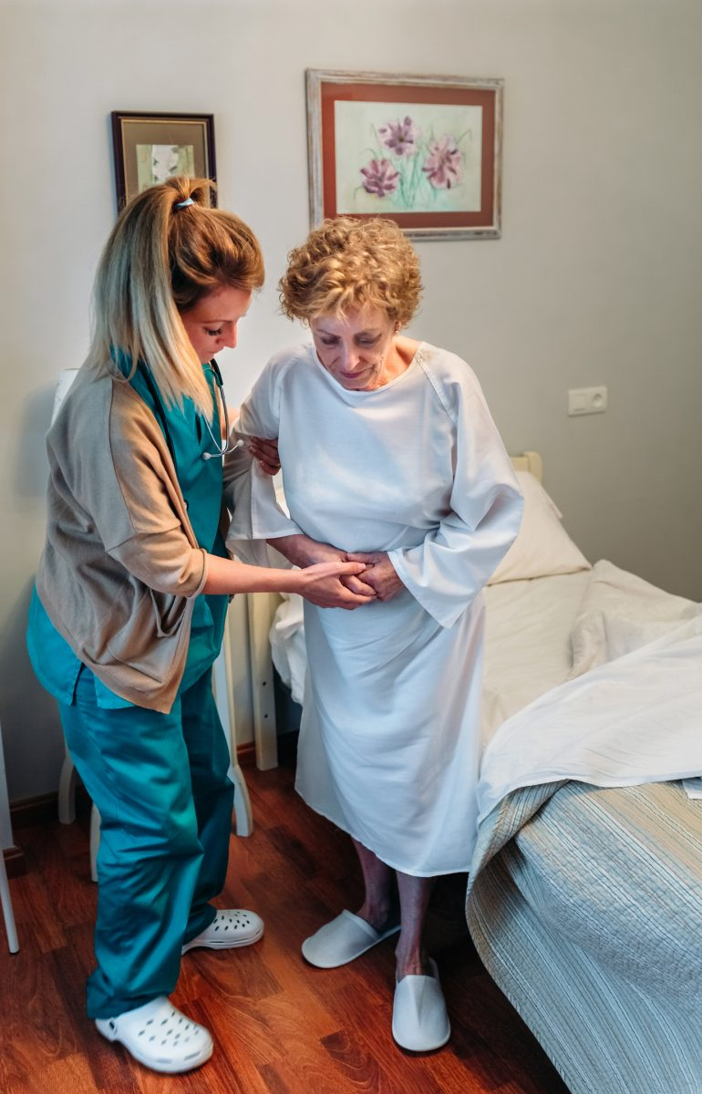 Female caregiver helping elderly female patient to stand up