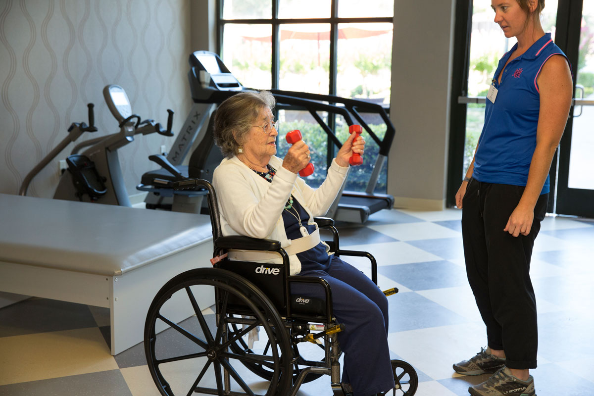 resident in a wheelchair lifting small hand weight during therapy session