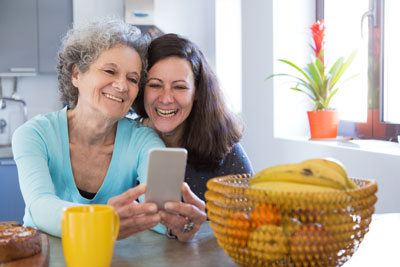 Woman looking at mobile phone with caregiver.