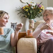 senior woman and caregiver drinking coffee together