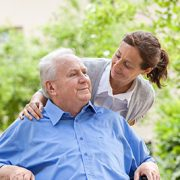 woman caregiver smiling with senior man outdoors