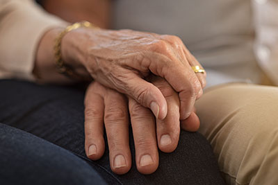 close-up of a senior couple's hands clasped together