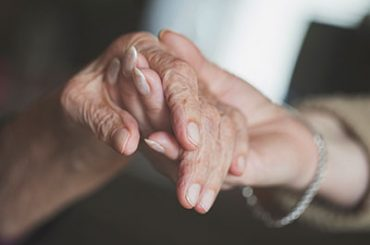 daughter holding hands with senior mother