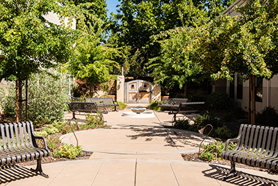 The Reutlinger Community outdoor patio with fountain and benches