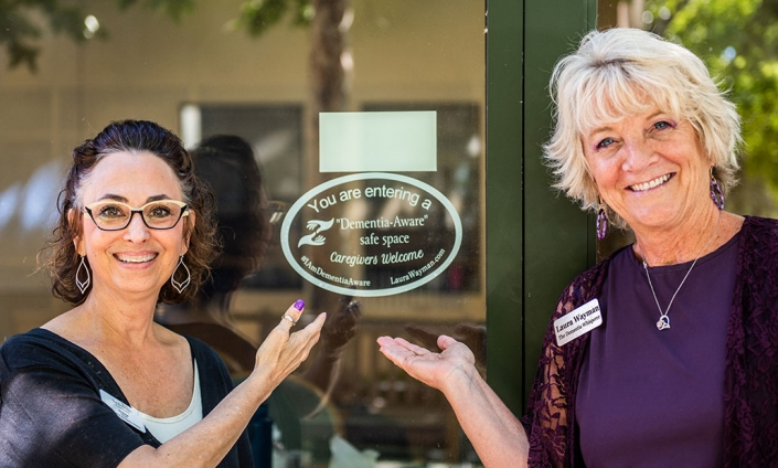 Two smiling staff members at the front door of memory care