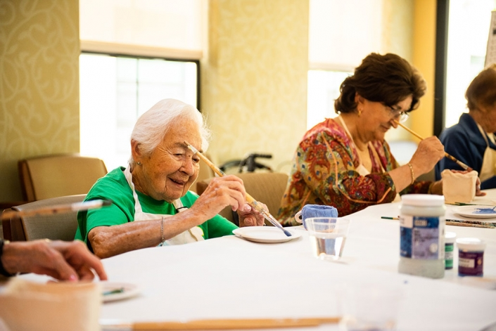 smiling residents enjoying painting pottery in an arts class