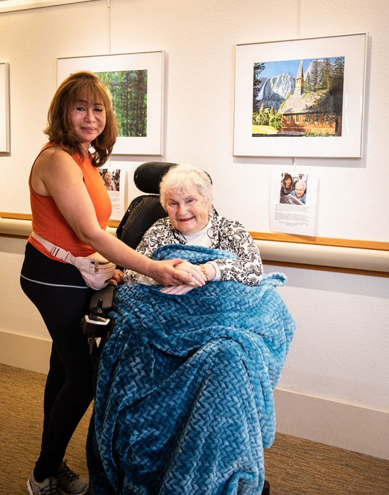 smiling caregiver, holding hands with resident in a wheelchair