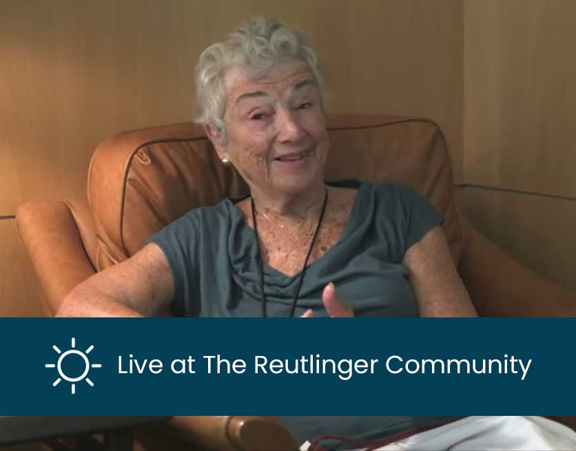 Living at The Reutlinger Community with a smiling woman sitting in a chair.