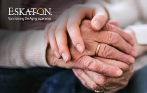 Younger hands holding older hands with care.