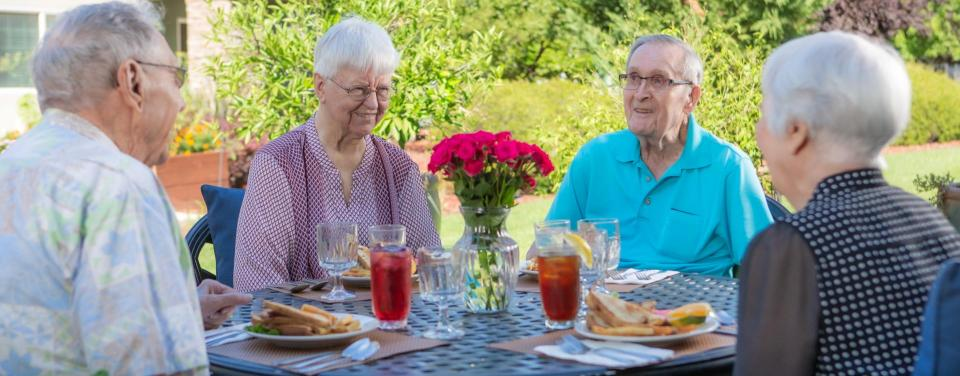 Four smiling residents have lunch together on the outside patio